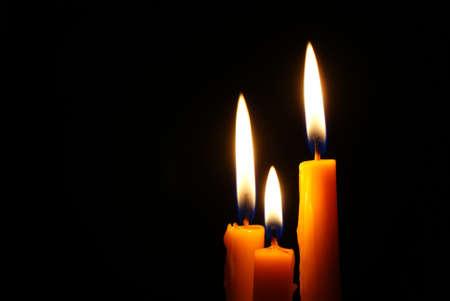 Closeup of burning candle isolated on black background Stock Photo