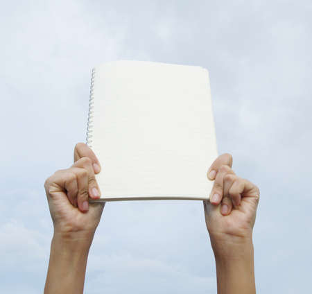 Female hands holding a blank white notebook    photo