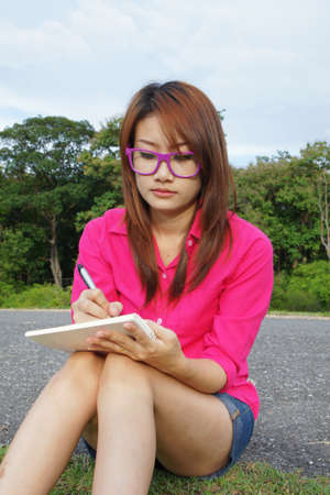 Asian student sitting at outdoors, studying and writing. Stock Photo - 10569927