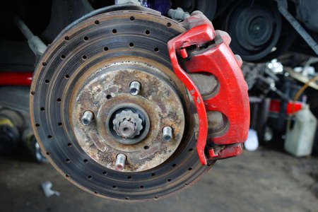 Rusted disc brake and caliper on car photo