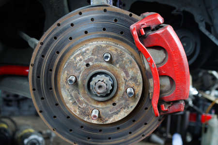 caliper: Rusted disc brake and caliper on car