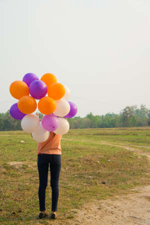 a happy woman holding balloons photo