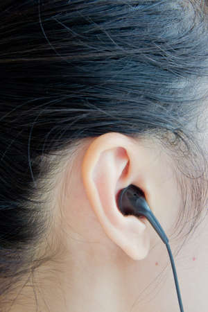 Human ear with earphone close-up Standard-Bild