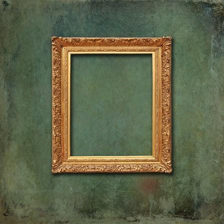 elegant frame: Empty golden vintage frame on a scratched grunge wallpaper with faded design