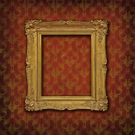 Empty vintage golden frame on a damask red ornated wallpaper
