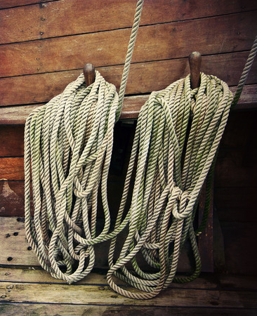 Ropes fastened around cleats on an old sailboat photo