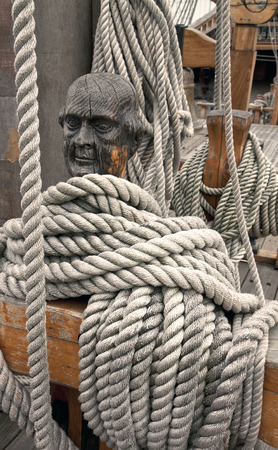 Ropes around a head shaped wooden cleat on an old vessel