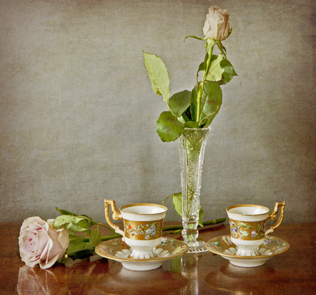 frugal: two beautiful blossoms of pink roses, two espresso cup and a crystal vase on a wooden table with a grunge background Stock Photo