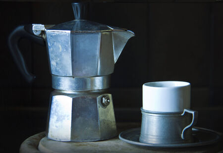 a typical Italian moka coffee maker worn and used and an espresso cup photo