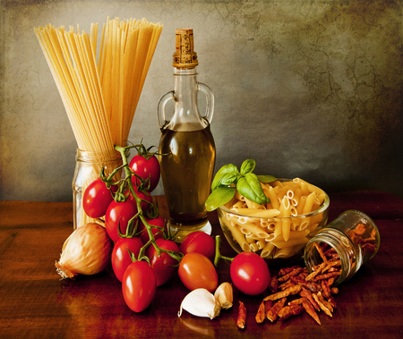 On the kitchen table the ingredients for a tasty and spicy arrabbiata sauce   tomatoes,basil,chili, garlic,onion, olive oil  Use on every kind of noodles  penne, spaghetti, linguine  photo