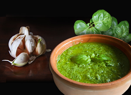 Bowl of pesto alla genovese, Italian recipe for an exquisite noodles sauce, garlic and basil, two of the main ingredients along with olive oil, parmesan cheese and pine nuts
