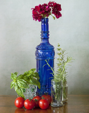 Decorative blue glass bottle with the product of my garten  tomatoes, basil rosmary and a red geranium flower photo