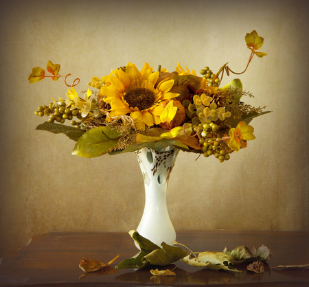 An autumnal bouquet, with sunflowers, grapes and leaves in a vase and dry leaves on a wooden table photo