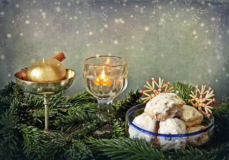Christmas still life: golden candle in a glass, golden apple with cinnamon, almond and raisin butter cookies, straw ornaments and a glitter of little stars. photo