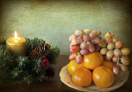Grunge and simple Christmas: wreath with golden candle and a dish of mandarins and grapes photo