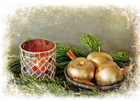 Chistmas time: a candle lit in a glass vase, a bowl with golden apples and cinnamon sticks framed in white photo