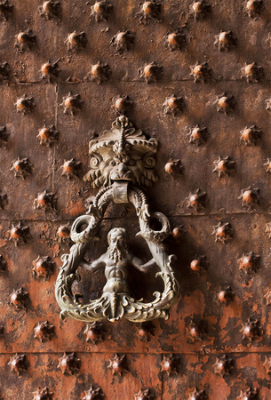 Ancient gate with bossed decoration and door knocker photo