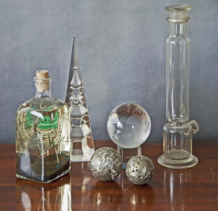 globe  the terrestrial ball: Interior still life, glass objects on a wooden table, a bottle with a butterfly,two metal balls,a chemistry glass tube and a terrestrial globe