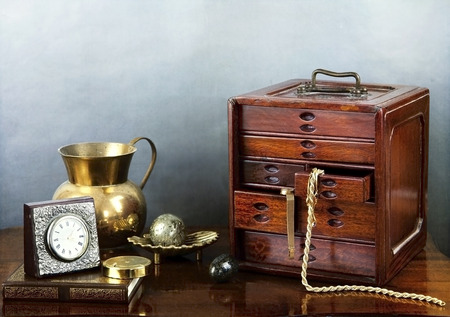 jewel case: Wooden jewel case with golden necklace, desk clock, brass jug, old book and carved stones Stock Photo