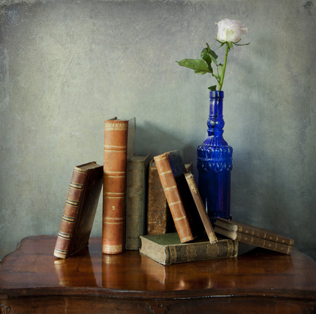 Interior still life: vintage composition of antique books on a wooden table and a single pink rose in a glass blue decorated bottle photo