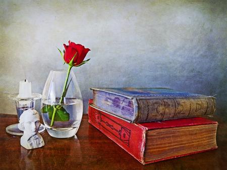 antiquary: Dos libros antiguos en una mesa de madera, una sola rosa en un florero de cristal, un peque�o busto de un poeta y de la vela Foto de archivo