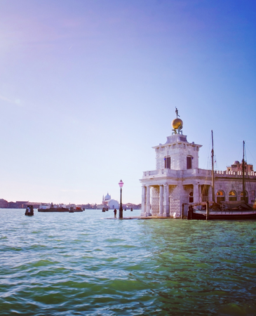 surmounted: VENICE, ITALY: Ancient custom house in Venice, surmounted by a wind vane bronze statue symbolizing the Fortune, retro effect Instagram-like added Stock Photo