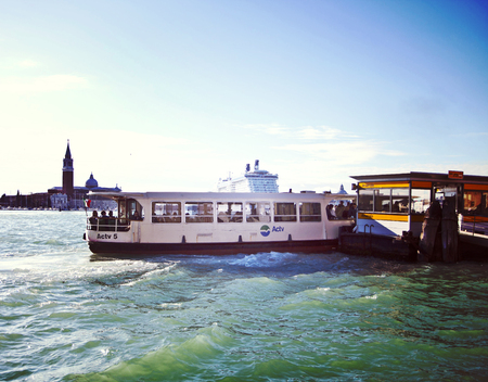 VENICE, ITALY: Water bus arrives at Arsenale landing stage, far behind S. Giorgio Island and a  big cruise ship, Vintage Instagram-like effect added.