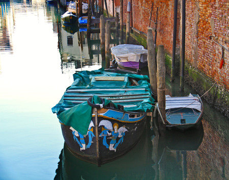 Romantic view of a corner of the popular side of Venice, less touristic but more lively, with boats floatig on the still waters of a canal. photo