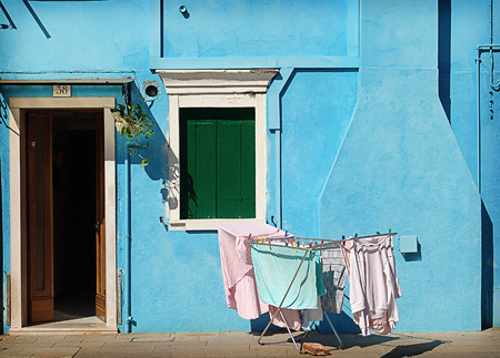 A beautiful day of September in Burano, a little blue house with the washing in the sun, a quiet place to stay. photo