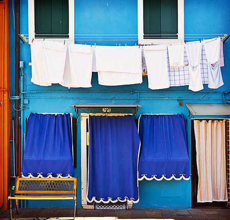 blue facade of a house of Burano, small fisher village in Venice lagoon, with laundry hanging from, the clothesline photo