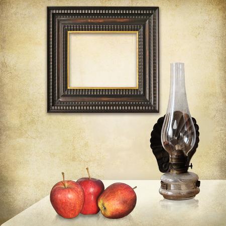 an oil lamp: retro naturaleza muerta, un marco vacío art deco, tres manzanas rojas, una vieja lámpara de aceite en un interior con textura grunge.