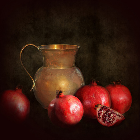 A still life like an old painting, dark with a dramatic use of lighting.A worn jug and some pomegranates in chiaroscuro.