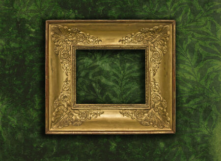 Vintage carved golden frame on grunge wallpaper with green leaves photo