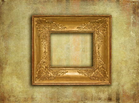 Golden wood carved ancient frame on a grunge wall covered with faded paper. photo
