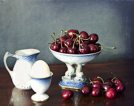 Bowl of red and ripe cherries on a wooden table, a milk jug and a boiled egg on a eggcup