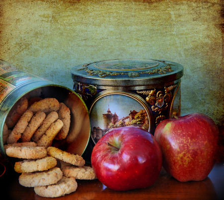 food on the table: two red apples and homemade cookies in vintage  metal decorated box