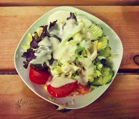 biergarten: salad bowl on a wooden bench at an open air restaurant (Biergarten) : lettuce, tomatoes,carrots, gerkins with awhite creamy dressing.