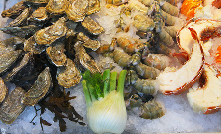 Display of fresh oysters and sliced lobsters on ice at the fish market photo