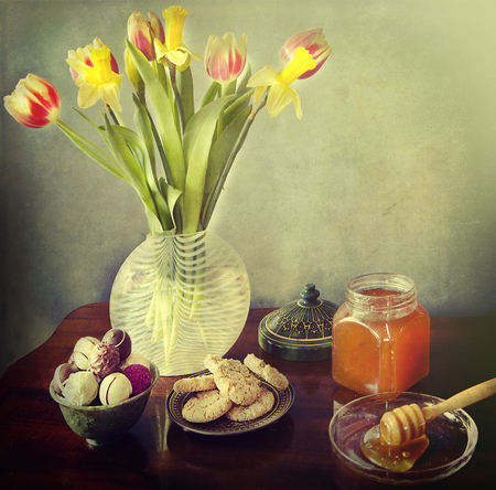 Vintage effects, glass vase with tulips, chocolate pralines,cookies and honey jar with dipper photo