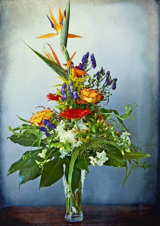 huge and elegant  bouquet of bird of paradise and other mixed flowers on a grunge background photo