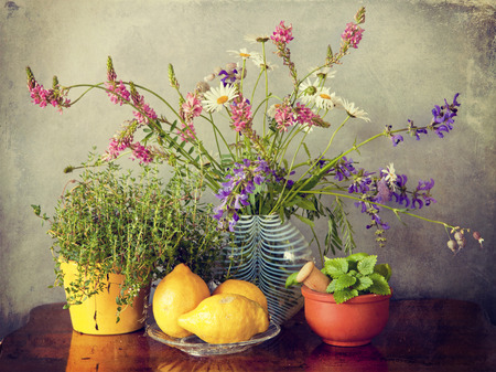 field of flowers: Garden herbs, field flowers in vase and lemon fuits with grunge texture and Instagram-like retro effect