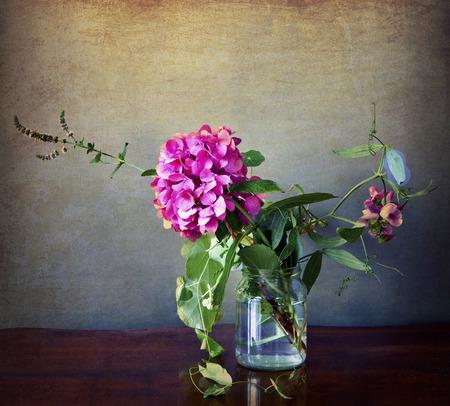 champ de fleurs: Fleurs d'hortensia rose et sur le terrain dans un verre avec texture vieux