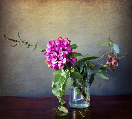 field of flowers: Pink hydrangea and field flowers in a glass with vintage texture