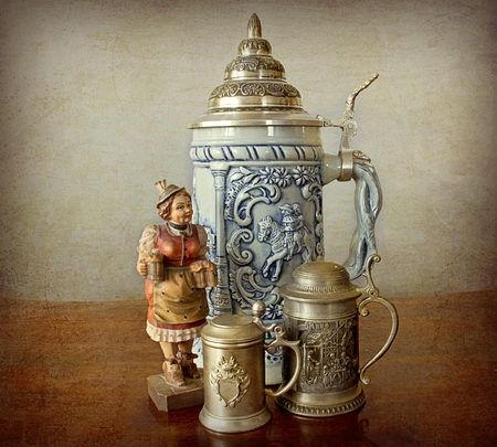 Traditional bavarian souvenirs -  pewter and ceramic beer mugs, a beer related wood carved figurine  on a grunge and vintage background