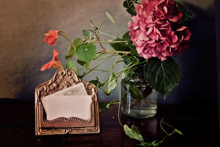 champ de fleurs: Fleurs d'hortensia et le terrain rose dans un verre � proximit� d'un brassholder de carte r�tro avec texture vintage et effdects Instagram-like