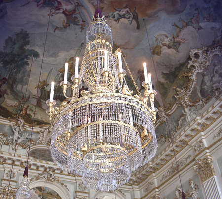 Antique crystal chandelier against a ceiling with frescoes and stucco