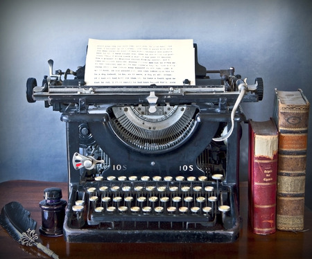 still life: Old typewriter on a wooden desk, with a paper sheet of faded characters, old books, ink and pen with grunge background