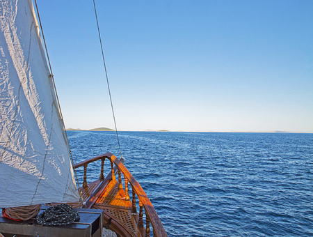 prow: Prow and mizzen of a wooden yacht traveling to Kornaty islands on bright summer day.