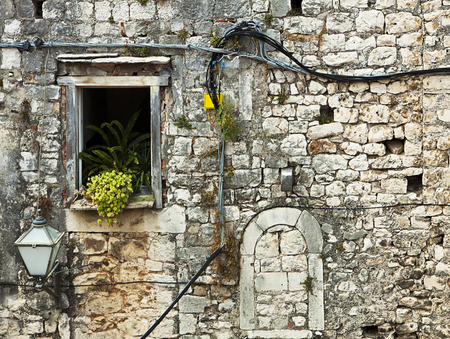 Facade of old Dalmatian house made of mortar and stone blocks with window, plants, flying electric cables and a street lamp