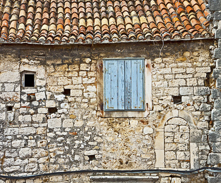 tile of roof: Facade of old Dalmatian house made of mortar and stone blocks with curved red tiled roof Stock Photo